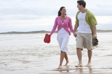 Romantic Couple Walking Along Summer Beach