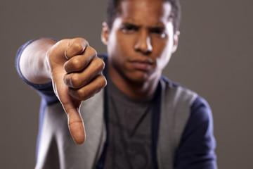 scowling dark young man showing thumb down