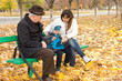 Grandfather, mother and little boy on a park bench