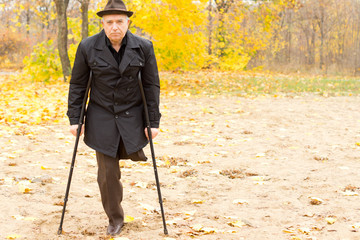 One-legged man walking with crutches in the park