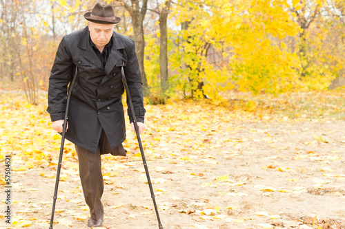 Elderly disabled man on crutches in a park