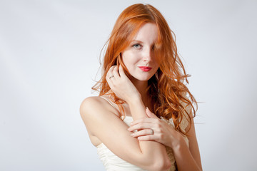 beauty shot of a young blue eyed woman with her red hair
