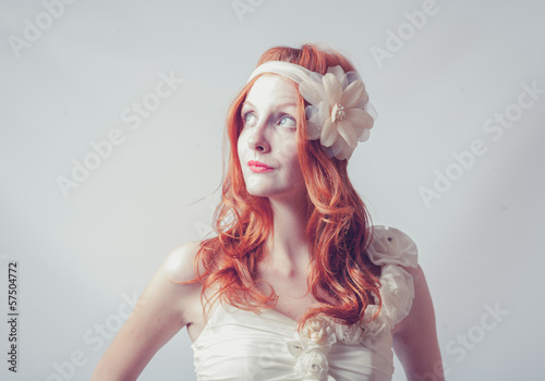 Portrait of a beautiful red haired woman with flower in her hair