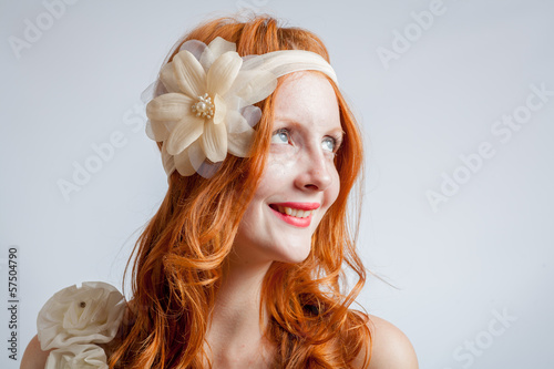 Portrait of a beautiful red haired woman with flower in  hair.