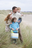 Family Walking Along Winter Beach With Picnic