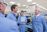 Technicians in lab coats talking in hi-tech manufacturing plant