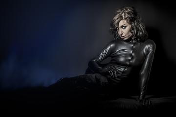 Beautiful brunette woman wearing latex dress on dark background,
