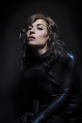 Beautiful brunette woman wearing latex dress on dark background