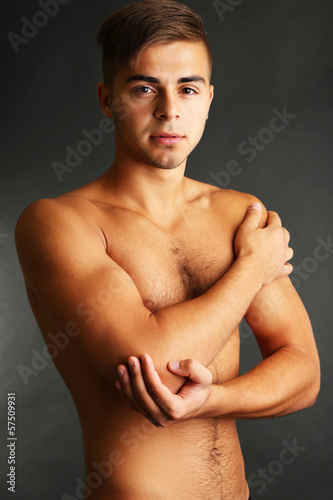 Young man with hand pain on grey background