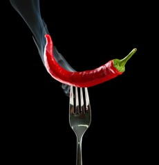 Red hot chili pepper  on fork, isolated on black