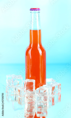 Drink in glass bottle with ice cubes on blue background