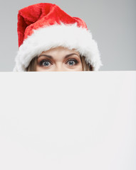 Close up christmas woman portrait behind big white card. Emotio