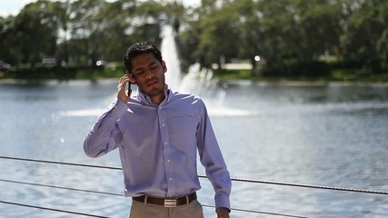 Angry businessman talking on the phone. outdoors