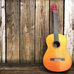 Acoustic wooden guitar leaning on a wooden fence. © storm
