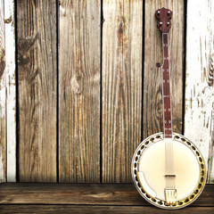 Banjo leaning on a wooden fence. Room for advertisment © storm