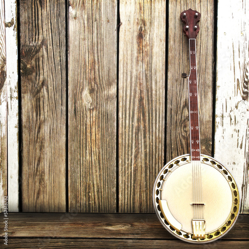 Banjo leaning on a wooden fence. Room for advertisment