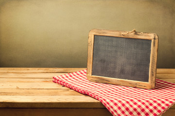 Retro chalkboard on tablecloth on wooden table