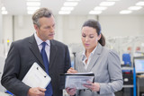 Businessman and businesswoman reviewing paperwork in manufacturing plant