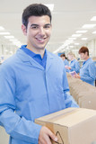 Portrait of smiling worker holding cardboard box in manufacturing plant