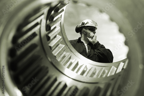 engineer seen through a giant gears axle