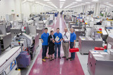 Portrait of business people and engineers in aisle of manufacturing plant