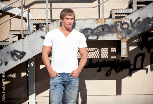 man in white t-shirt posing against metal staircase