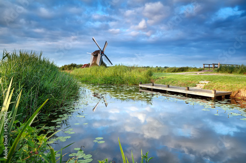 blue sky and windmill reflected in river