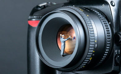 Miniature man cleaning camera lens