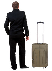 back view of business man in black suit traveling with suitcas .