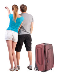young couple traveling with suitcas and pointing at wal Back vie