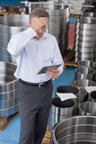Businessman with head in hands using digital tablet among steel roller bearings in manufacturing plant