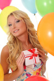 beautiful blonde with a gift on the background of balloons