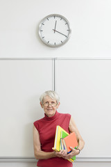 Lehrerin vor der Tafel mit Büchern und Uhr