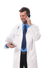 Doctor with mobile phone checking something on digital tablet