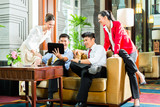 Asian Chinese business people meeting in hotel lobby