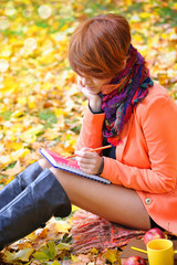Red-haired student girl with notebook on a background autumn