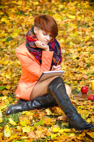Red-haired student girl with notebook