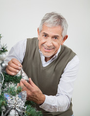 Senior Man Decorating Christmas Tree