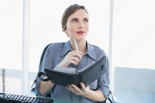 Thinking businesswoman holding her diary while sitting at her de