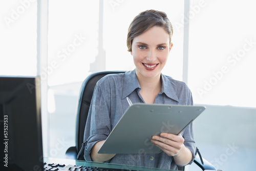 Portrait of beautiful businesswoman holding a clipboard sitting