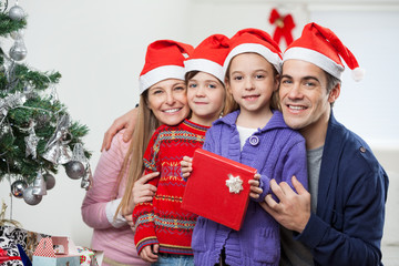 Parents And Children With Christmas Gift