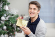 Happy Man Holding Gift By Christmas Tree