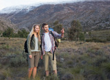 Fit young couple with backpacks on landscape