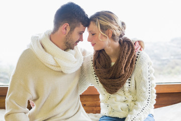 Loving couple in winter clothing against window