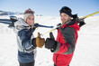 Smiling couple with ski boards gesturing thumbs up on snow