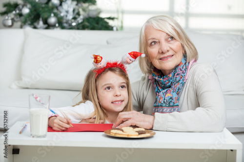 Girl And Grandmother With Cardpaper At Home