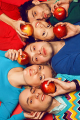 Five stylish friends hugging and lying together with apples