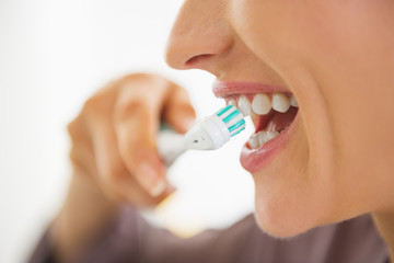 Closeup on happy young woman brushing teeth