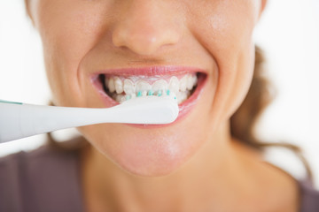 Closeup on happy woman brushing teeth
