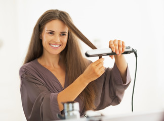 Happy young woman straightening hair with straightener